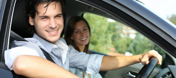 smiling couple posing inside their car
