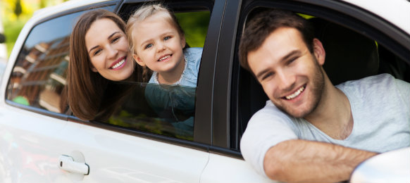 family smiling inside their car