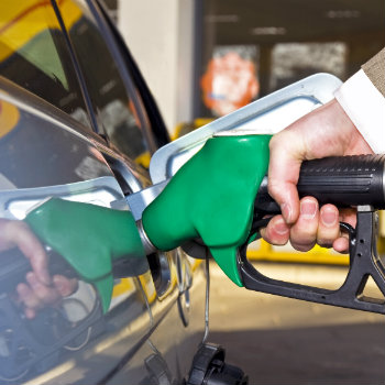 a mans hand filling up a rental car with fuel