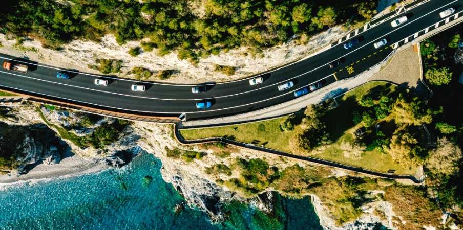 aerial view of road going along mountain and sea