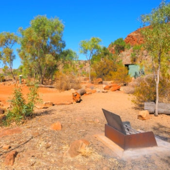 Camp ground with fire pit at remote N'Dhala Gorge near Ross River Station, Northern Territory, AU
