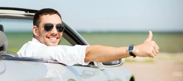 dapper guy smiling inside his car rental