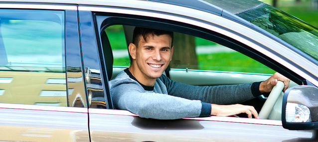 smiling guy posing inside his car