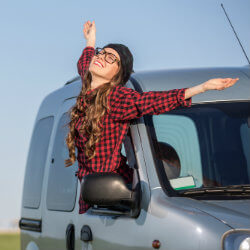 carefree woman looking out the car rental window