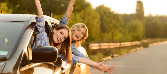 two happy women with arms outstretched outside the car window
