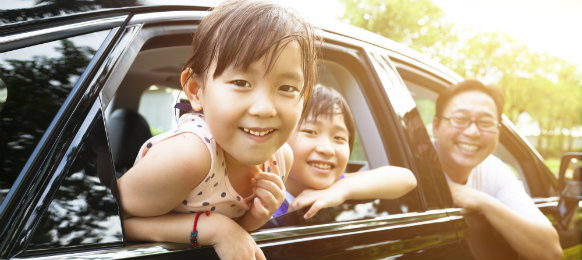 children and their father in a car
