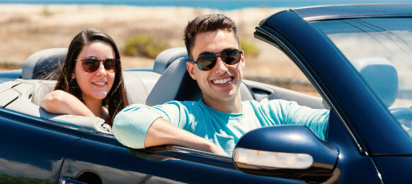 couple inside a blue rental car
