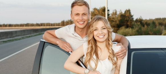 couple posing beside their white car