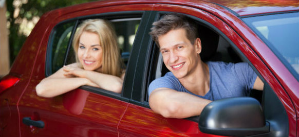 couple smiling while riding a car hire