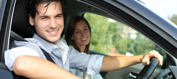 couple smiling inside their rental car