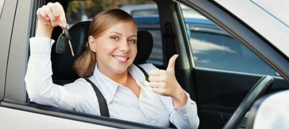 cheerful girl showing a thumbs up and a key
