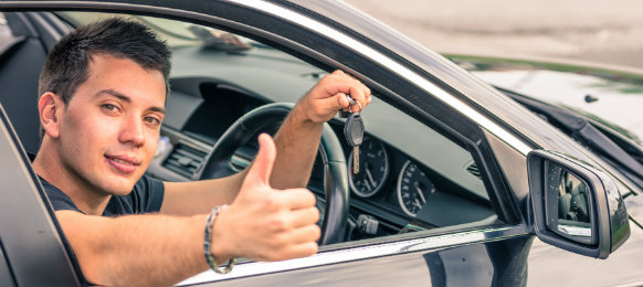 happy guy showing off his key inside his car