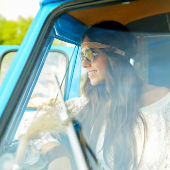 happy young hippie girl in a minivan