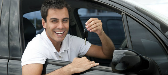 latino guy holding car key inside a car hire