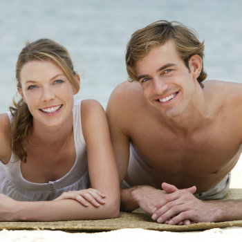 lovely couple lying on beach mat