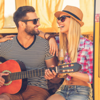man playing guitar with his girlfriend