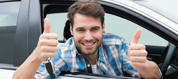 man giving a thumbs up in his car hire