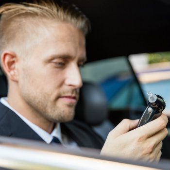 man looking at his beathalyzer test inside his car hire