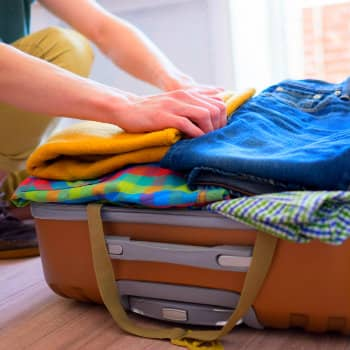 Man packing several clothes in a suitcase