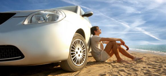 man sitting beside his car rental parked on the beach