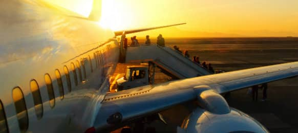 Passengers boarding in an aircraft at sunset