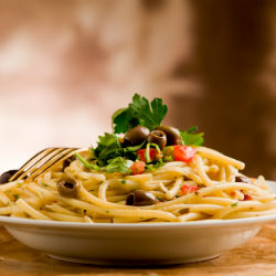 pasta with olives and parsley on a plate