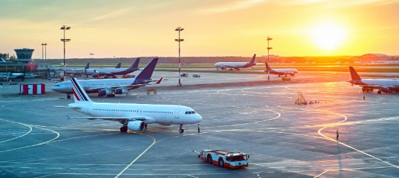 planes parked at the airport terminal during sunset