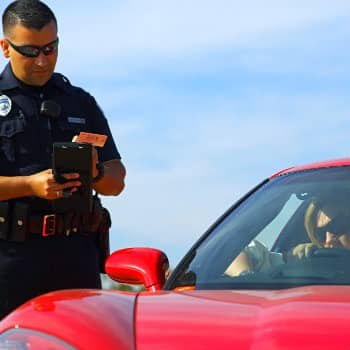 Policeman issuing speeding ticket to the driver