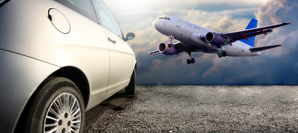 side view of a car hire and flying airplane