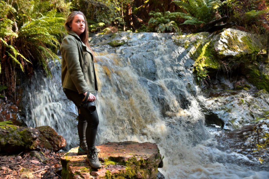 Megan Jerrard beside a waterfall in Tasmania