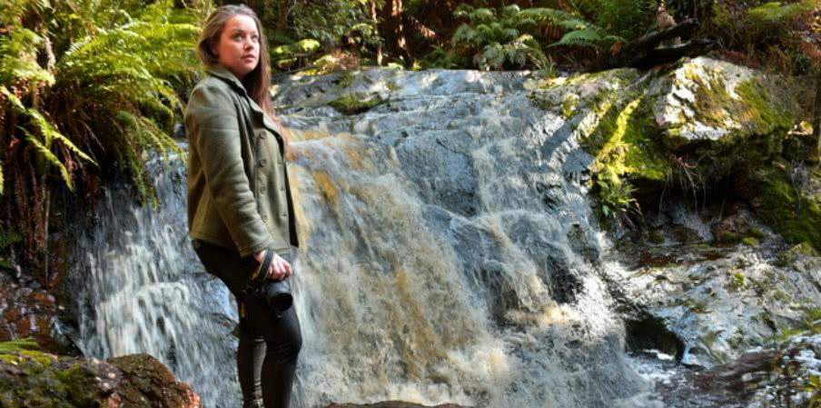 Megan Jerrard beside a waterfall in Tasmania