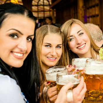 three women drinking beer and celebrating oktoberfest in australia