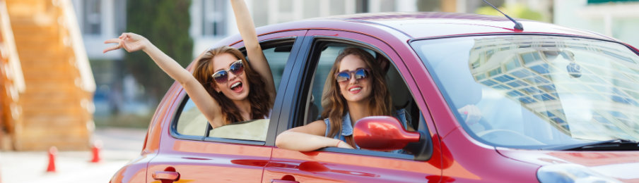 two female friends enjoying driving around town