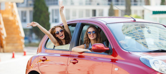 two girls celebrating inside their rental car