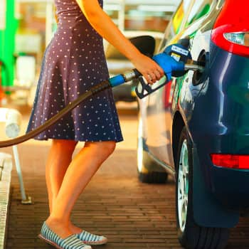 Woman filling up her car with gas for a long road trip
