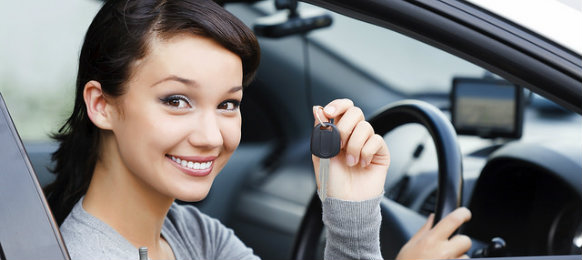 smiling woman holding a car key in a car hire