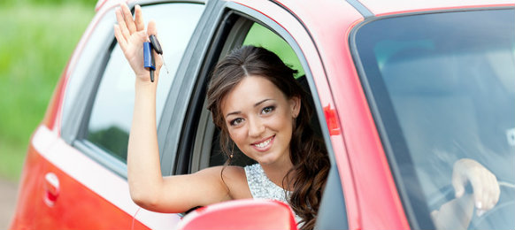 woman holding car key in a red car