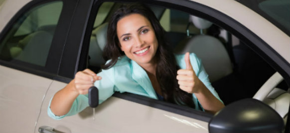 woman holding car key and giving a thumbs up