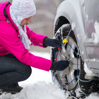 Woman putting a snow chain on her car tyre