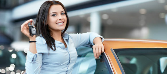 woman standing beside a car and holding a car key
