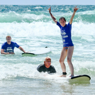 Woman learning how to surf thorugh Coolum Surfing School