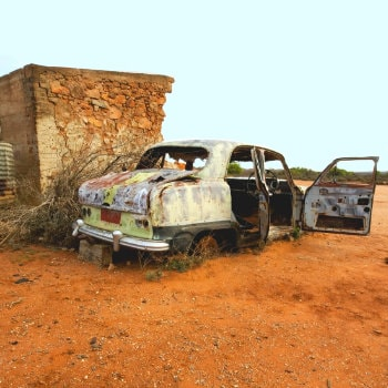 wrecked car and ruined stone house in silverton outback nsw