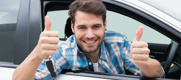 young professional smiling inside his car