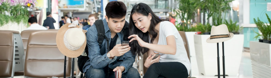 young couple travellers booking a car using their phone